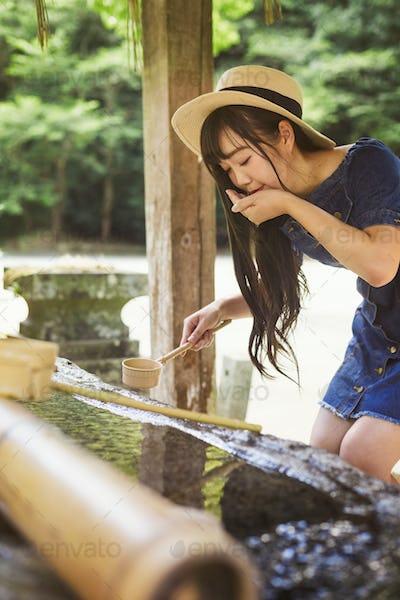 Young woman using bamboo water hand washing basins at shrine
