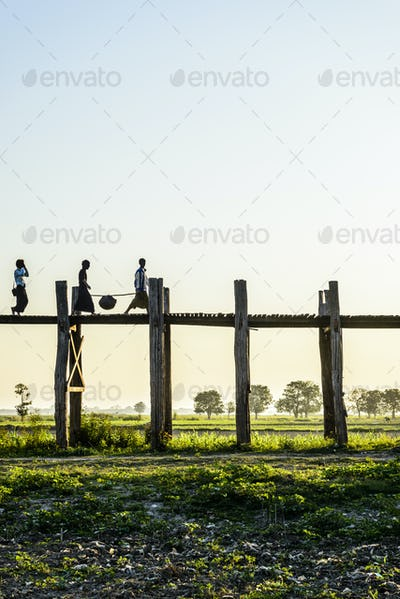 People walking on elevated wooden walkway in rural landscape