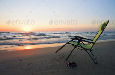 Lounge chair on beach at sunset