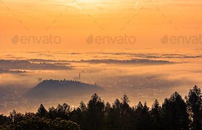 Graz city covered if fog on autumn morning during sunset