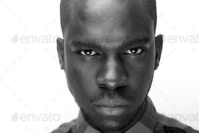 Close up black and white of young black man staring