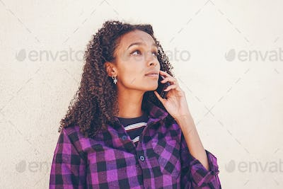 Young casual woman using her smartphone