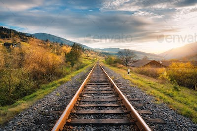 Railroad in mountains at sunset in autumn