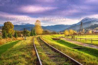 Railroad in mountains with snowy peaks at sunset in autumn