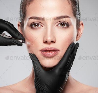 Caucasian woman getting botox cosmetic injection in forehead. Woman gets botox injection in her face