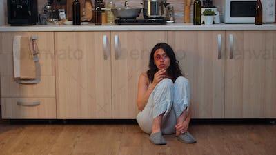 Injured woman smoking sitting on the floor