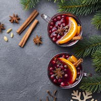 Mulled red wine with spices. Christmas decoration. Grey stone background. Copy space. Top view