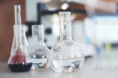 Flask with blue purple pink liquid laboratory cork stand on the table in the test laboratory fluid