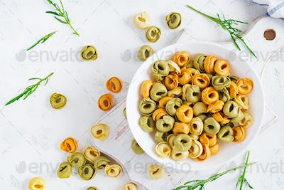 Raw cheese filled tortellini pasta in white bowl. Italian pasta. Top view, flat lay, overhead