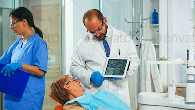 Orthodontist using tablet to explain dental xrays to patient
