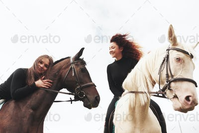 Two young pretty girls riding a horses on a field. They loves animals andhorseback riding