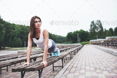 A beautiful athlete brunette performs outdoor exercises