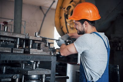 Portrait of a young worker in a hard hat at a large metalworking plant. The engineer serves the