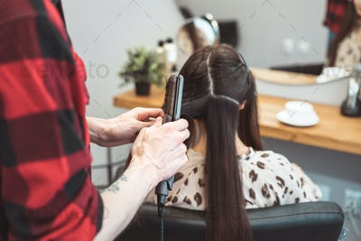Hair stylist barber styling long hair with hair iron for young woman in beauty salon