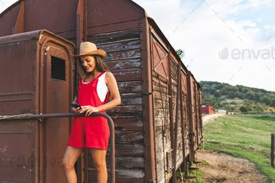 Beautiful Young girl Smiling and Using Smartphone at the Back of an Old Vintage Train Wagon