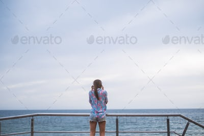 Rear view young lady caucasian woman standing at the beach