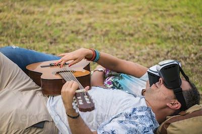 nice modern couple man and woman caucasian play guitar