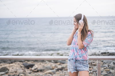 beautiful young lady caucasian woman standing at the beach with headphones