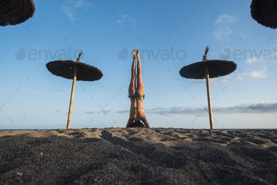 beautiful young female in reverse yoga position at the beach