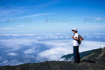 Lonely retired adult white hair man standing during a trekking travel adventure