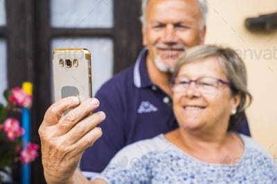 cheerful happy old mature adult man and woman taking selfie with the phone at home