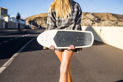 blonde young woman viewed from rear walking down the street with skate board