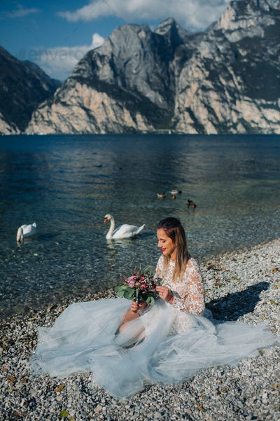 a girl in a smart white dress is sitting on the embankment of lake Garda.A woman is photographed