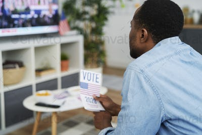 Close up of man interested in watching TV of election