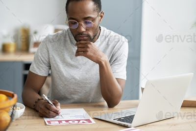 Young black man fulfilling document of mail voting