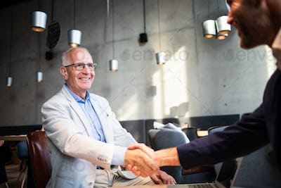 Senior businessman shaking hands during meeting in cafe