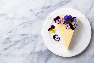 Cheesecake Decorated with Edible Flowers on white plate. Marble background. Copy space. Top view.