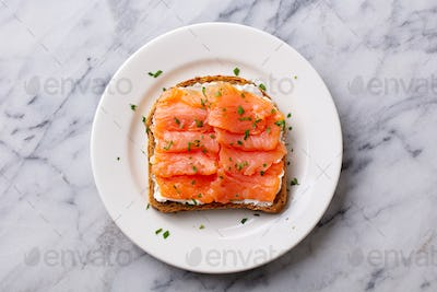 Sandwich, Toast with Smoked Salmon and cream cheese on white plate. Marble background. Top view.