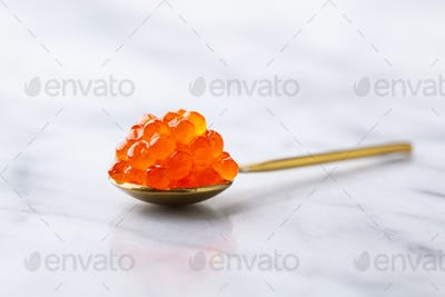 Red Salmon Caviar in golden spoon. Marble background. Close up.