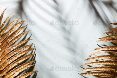 Gold palm leaves and shadows on a blue wall background.