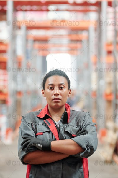 Young mixed-race worker of warehouse in grey uniform crossing arms by chest