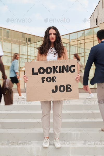 Young jobless woman holding piece of cardboard with notice of looking for job
