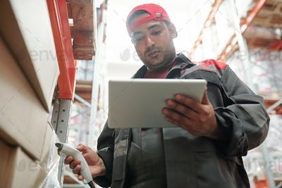 Young serious mixed-race worker of warehouse looking at tablet display at work