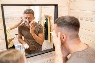 Young cheerful man applying foam on beard while his little daughter helping him