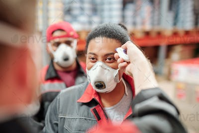 Contemporary factory worker of warehouse having her temperature measured