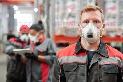 Confident young man in workwear and protective respirator looking at you