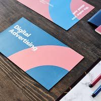 Two brochures with digital advertising brief course surrounded by documents