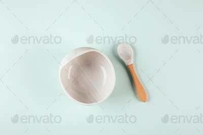Grey silicone dishware plate and spoon on background. Serving baby, first feeding concept. Flat lay