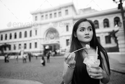 Young beautiful Asian tourist woman eating street food