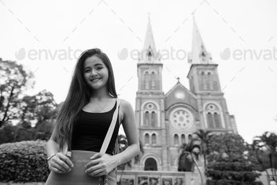 Happy young beautiful Asian tourist woman against view of cathedral