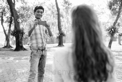 Happy Indian man smiling and taking picture with mobile phone while looking at beautiful woman in