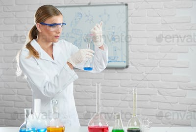The young scientist works with chemical liquids