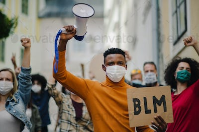 Group of people activists protesting on streets, BLM demonstration and coronavirus concept.