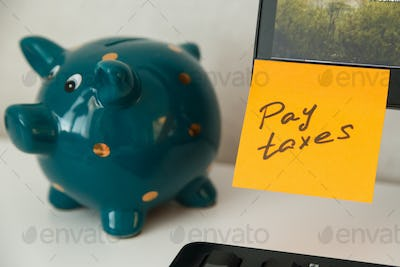 Reminder pay taxes sticked on monitor at freelancer's workplace