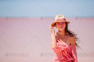 Woman in hat walk on a pink salt lake on a sunny summer day