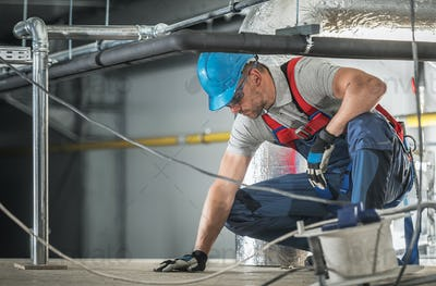 Caucasian HVAC Worker Wearing Safety Harness at Work